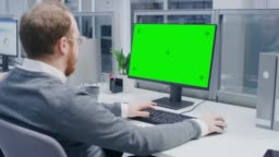 Over the Shoulder Shot of Motivated Office Worker Using Green Mock-up Screen Desktop Computer in the Big Bright Open Space Office