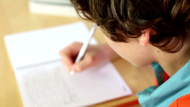 over the shoulder view of kid doing homework - homework stock videos & royalty-free footage