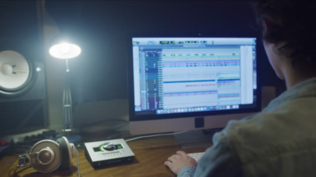 over the shoulder view of man using computer at night in music studio / provo, utah, united states - editor stock videos & royalty-free footage
