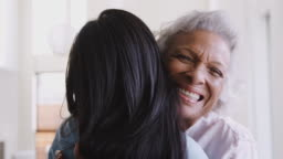 Over The Shoulder View Of Senior Mother Being Hugged By Adult Daughter At Home
