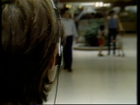 over the shoulder view of someone listening to a personal stereo - stereo personale video stock e b–roll