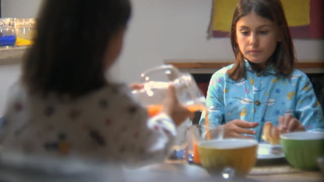 ms over the shoulder view of young sister at breakfast table as the eats a pastry and drinks orange juice/ rome, italy - juice drink stock videos and b-roll footage
