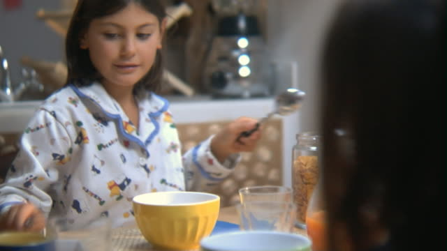 vídeos de stock e filmes b-roll de ms over the shoulder view of young sister at breakfast table hitting bowls and glasses with knives and forks/ rome, italy - utensílio