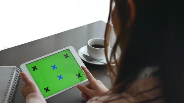 Sur l'épaule vue jeune femme à l'aide de tablette numérique avec écran vert afficher