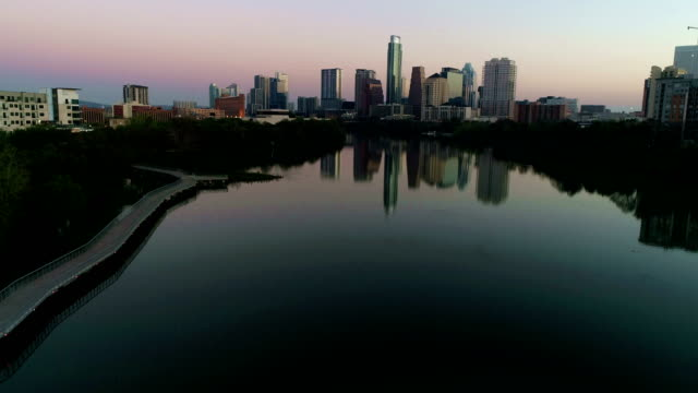 vídeos de stock e filmes b-roll de over town lake at sunrise austin texas capital city skyline during colorful tranquil morning - town