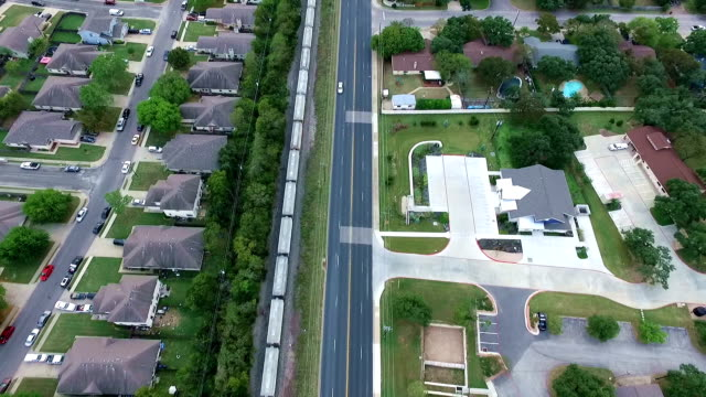 over train tracks aerial above homes and houses in suburb new modern development in central texas outside of austin, tx straight across city - modern rock stock videos & royalty-free footage