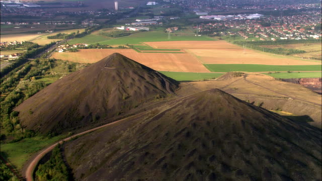 aerial over two large slag heaps surrounded by farmland and town/ lens, france - lens pas de calais stock videos & royalty-free footage