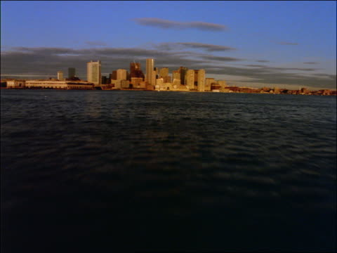 vidéos et rushes de low aerial over water towards boston skyline - boston