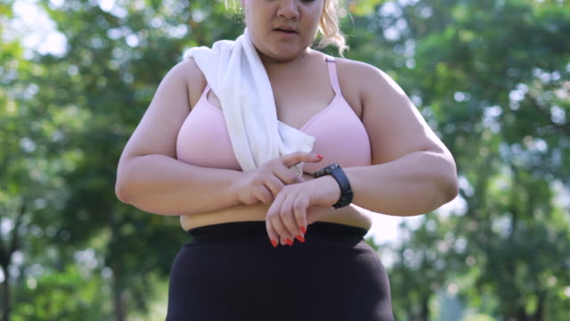 over weight woman run and setting smart watch - body positive stock videos & royalty-free footage