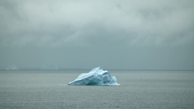 overcast arctic seascape with iceberg - iceberg ice formation stock videos & royalty-free footage