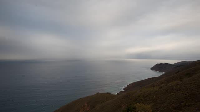 overcast clouds pass over coastline - 丘点の映像素材/bロール