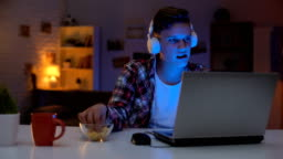 Overemotional teen playing computer game on laptop and eating snacks, addiction