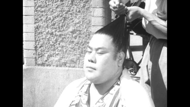 vídeos de stock e filmes b-roll de overexposed shot of attendant fixing sumo wrestler's hair / [normal contrast] vs attendant ties up wrestler's hair as small children look on / vs... - cross legged