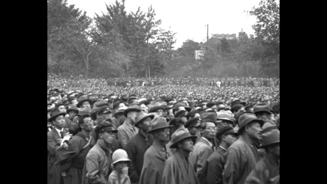 overflow crowds outside stadium looking at scoreboard in bg man's head turns looking at camera / pan huge crowd / crowd looking up at scoreboard /... - 1920年点の映像素材/bロール