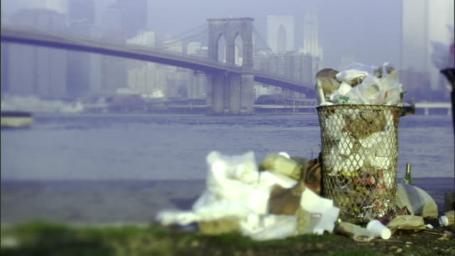 MS, SELECTIVE FOCUS,  Overflowing garbage cans with Brooklyn Bridge in background, New York City, New York, USA