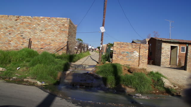overflowing water pipe into township street cosmo city south africa cosmo city is a new suburb of johannesburg only being developed in 2005 - water pipe stock videos & royalty-free footage