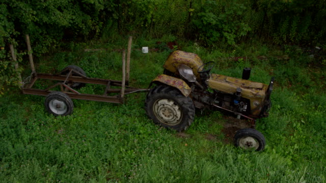 Overgrown farm with old abandoned tractor