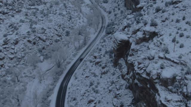 冬の砂漠の風景の中の雪に覆われた、岩が多い崖の横にある道に単一車のオーバーヘッド空中ドローン ショット - winter点の映像素材/bロール
