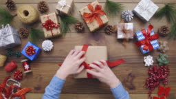 Overhead aerial footage of woman opening Christmas present at table