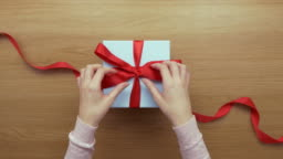 Overhead aerial footage of woman opening red ribbon on gift