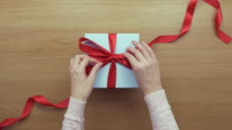 Overhead aerial footage of woman opening ribbon on empty gift