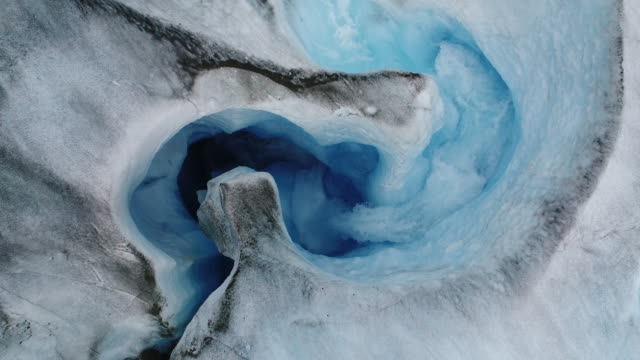 overhead aerial view of river of melting water on sawyer glacier in tracy arm, southeastern alaska - 氷河点の映像素材/bロール