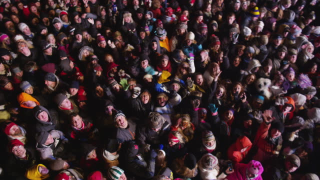 overhead boom shot of a cheering crowd spectators at a free outdoor concert venue during winter. - waving stock videos & royalty-free footage