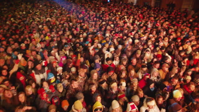 overhead boom shot of a cheering crowd spectators at a free outdoor concert venue during winter. - crowd stock videos & royalty-free footage