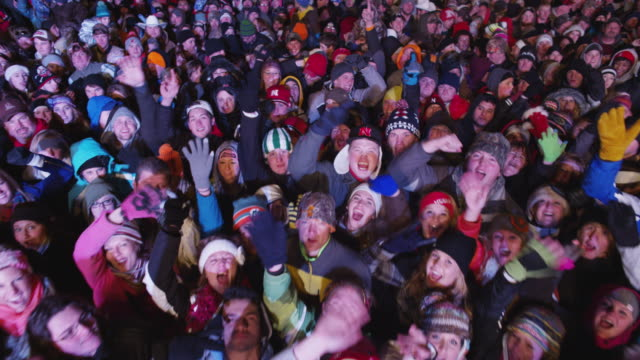 overhead boom shot of a cheering crowd spectators at a free outdoor concert venue during winter. - ライブイベント点の映像素材/bロール