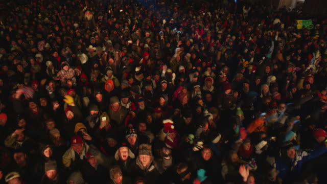 overhead boom shot of a cheering crowd spectators at a free outdoor concert venue during winter. - 腕を上げる点の映像素材/bロール
