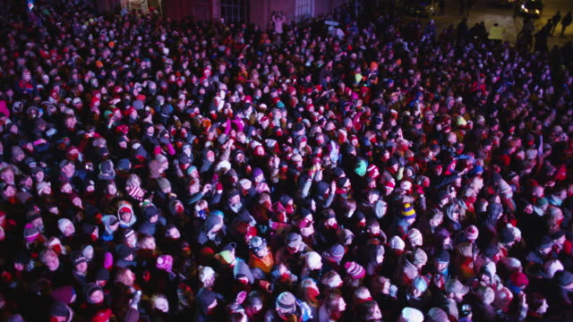 overhead boom shot of a cheering crowd spectators at a free outdoor concert venue during winter. - コンサート点の映像素材/bロール