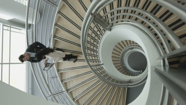 overhead business colleagues walking down spiral staircase discussing work - spiral staircase stock videos & royalty-free footage