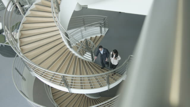 overhead business colleagues walking up spiral staircase discussing work - spiral staircase stock videos & royalty-free footage
