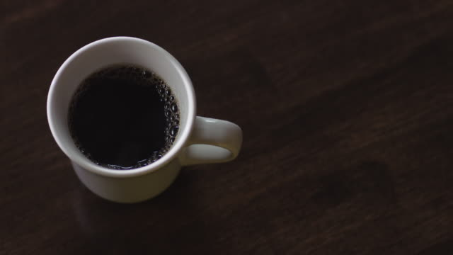 stockvideo's en b-roll-footage met overhead ceramic cup of coffee is picked up by a woman in a coffee shop. - grijpen