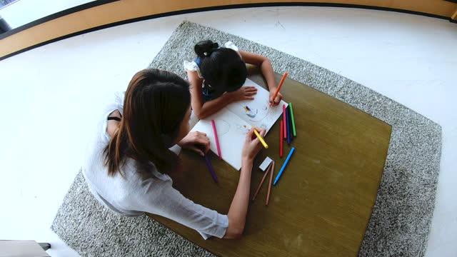 overhead chinese asian woman helping her child sketch - 消しゴム点の映像素材/bロール