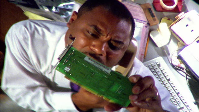 stockvideo's en b-roll-footage met overhead close up businessman examining circuit board while on telephone - it'er