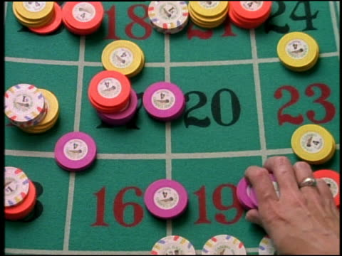 vídeos de stock, filmes e b-roll de overhead close up hand placing gambling chips on roulette board - enfoque de objeto sobre a mesa