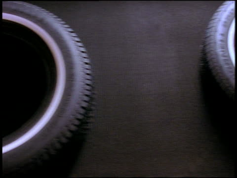 Overhead close up tires passing by on conveyor belt in factory