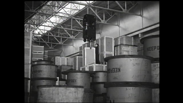 overhead crane lifting crates in the storage area with the help of a worker - 1940 1949 stock videos & royalty-free footage