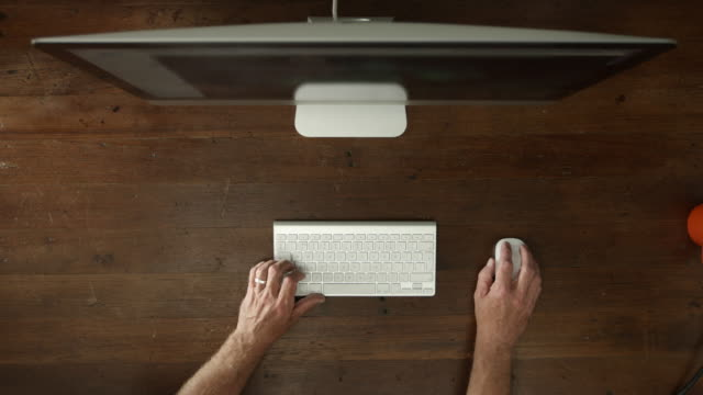 Overhead desk with desktop computer and male hands typing
