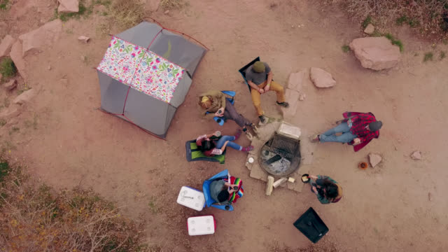 vídeos y material grabado en eventos de stock de overhead drone shot as group of friends on camping trip sit and talk around fire pit. - camping