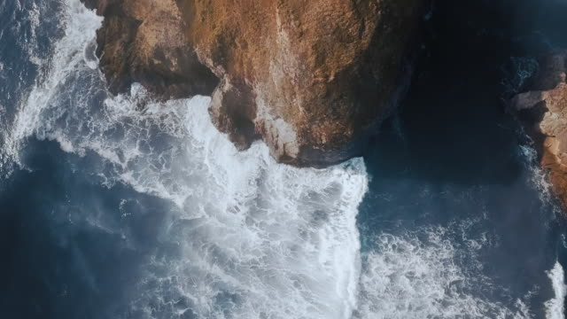 overhead drone shot of cliffs in rippling blue water (ariya's beach, oregon, usa) - 沿岸点の映像素材/bロール