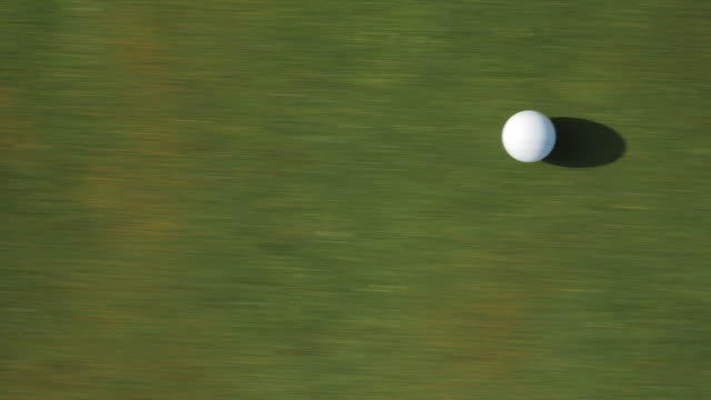 overhead, golf ball rolls on golf course - green golf course stock videos and b-roll footage