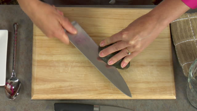 vídeos y material grabado en eventos de stock de overhead how to cut an avocado and remove the pit seed. - aguacate