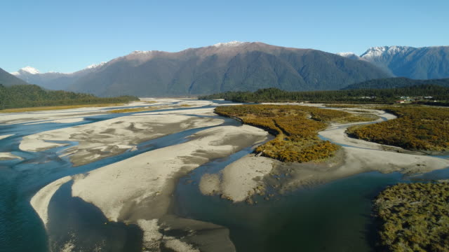 overhead looking at haast river with southern alps in background. - new zealand southern alps stock videos & royalty-free footage