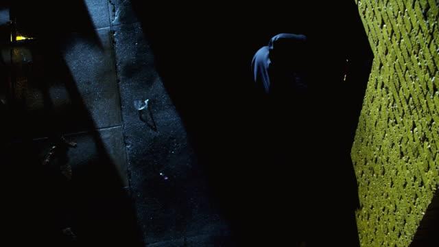 vidéos et rushes de ws overhead - man in hoodie walks to door in dark alleyway. the door opens spilling light into the alleyway, and he enters. - entrer