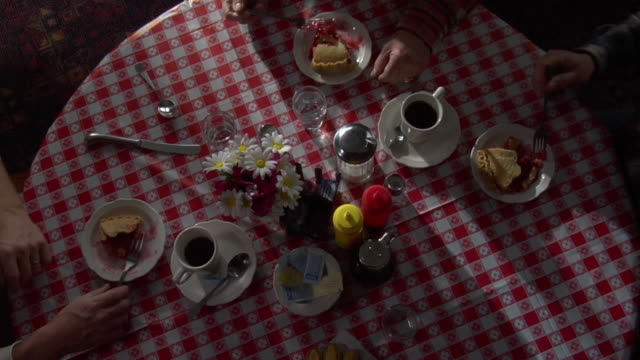 overhead of a table in a rural diner cafe , the arms of farmers can be seen with coffee and cherry pie. - tischtuch stock-videos und b-roll-filmmaterial