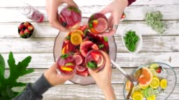 Overhead of friends hands toasting over punch bowl of sangria
