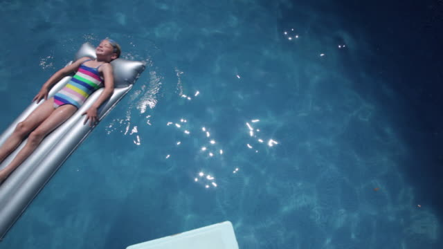 Overhead of girl aged 8 on silver lilo on open air pool floating across shot bottom left to top right with pan.