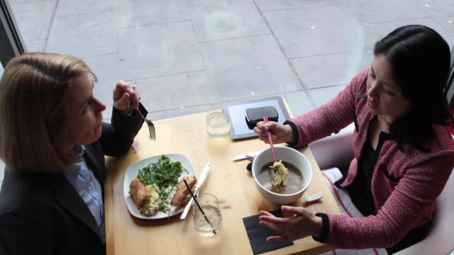 Overhead of two young, female business executives having a business lunch.